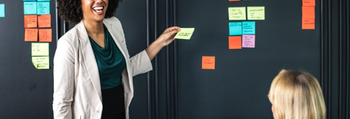 Woman putting post-it notes on wall.