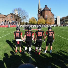 Four football players holding hands and facing the field.